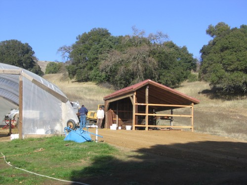 The new wash station sits across the road from the greenhouse. One of the three walls has been constructed.